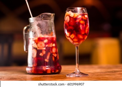 A bottle of sangria accompanied by a glass on a wooden table