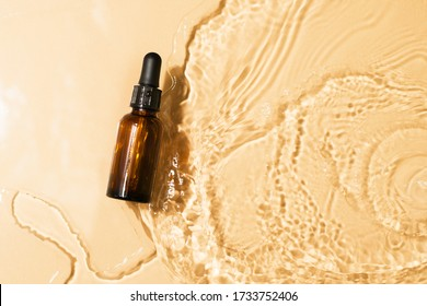 Bottle serum, oil cosmetic in clean transparent water with sunlight on beige background, flat lay, top view, copy space
