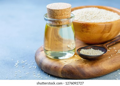 Bottle of sesame oil and white sesame seeds in a bowl on a wooden board, selective focus.