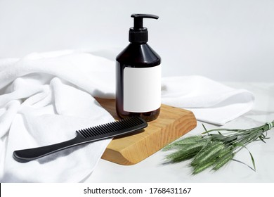 Bottle of shampoo, conditioner or hair mask with white towel, hairbrush, wood and herbs on a white background. Organic cosmetic. Treatment spa beauty skincare healthcare. Brand commercial. Product