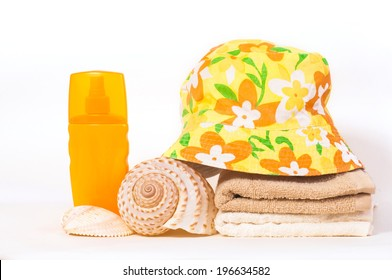 bottle of shampoo and towel seashells summer hat on a white background