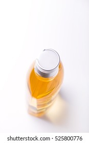 bottle of shower oil with almond oil in it, isolated on white background, brightly lit, copy space, top angle view