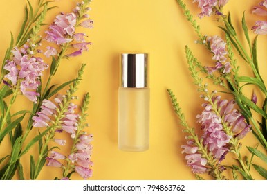 Bottle of skin care product framed aromatic fresh lilac flowers on bright sunny yellow background top viewed. Feminine beauty treatment.