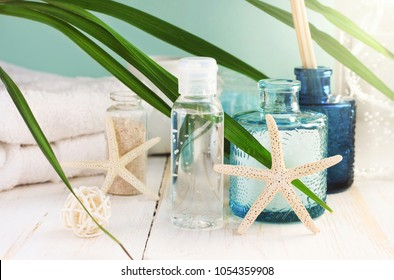 Bottle of skincare refreshing mineral tonic, sea salt in light blue glass jar, starfish. Beach styled bathroom relaxing decor with fresh palm leaf.