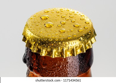 Bottle with soft drinks or alcohol in the ice. On gold caps and a bottle neck are drops of dew. Beer bottle cap close-up macro Isolated on white background with clipping path.