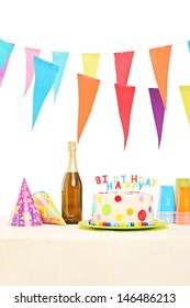Bottle of sparkling wine, plastic glasses, party hats and birthday cake on a table, isolated on white background