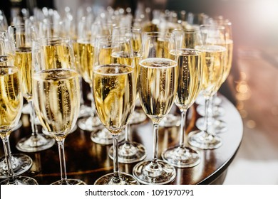 Bottle of sparkling wine with three flute glasses with bubbles floating up on gray backgrounds