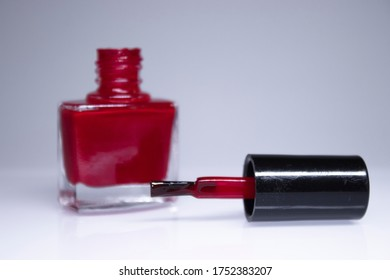 A bottle with spilled red nail polish on white background. nail lacquer. Nail manicure concept. Isolated, copy space.