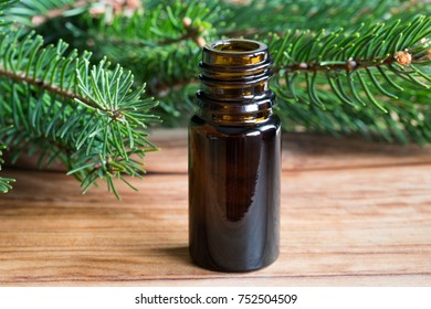 A bottle of spruce essential oil on a wooden table, with spruce branches in the background