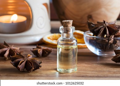 A bottle of star anise essential oil with star anise and an aroma lamp in the background