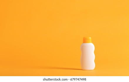 Bottle of sunblock on a yellow background