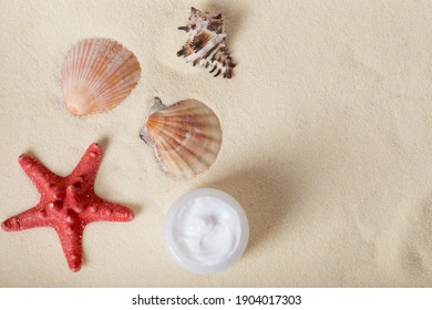 Bottle of sunblock with shells on sand. sun on the sand, shells and sunscreen