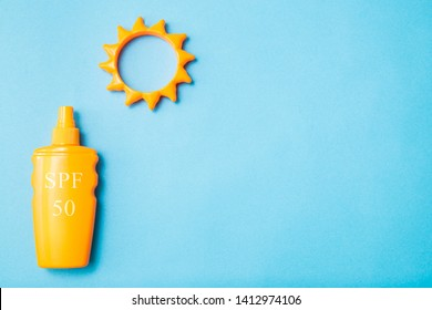 Bottle of sunscreen cream or lotion with SPF 50 and sun toy flat lay on the blue background with copy space. Spf summer skin protect.