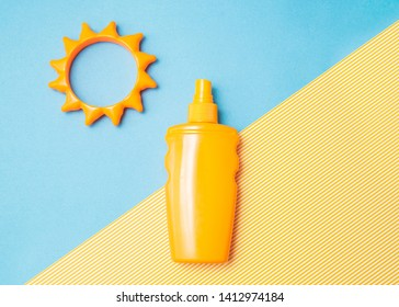 Bottle of sunscreen cream or lotion with sun toy flat lay on the blue and yellow background with copy space. Spf summer skin, uv protect top view.