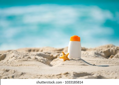 Bottle of sunscreen lotion and starfish on tropical beach, Beach accessories and summer concept