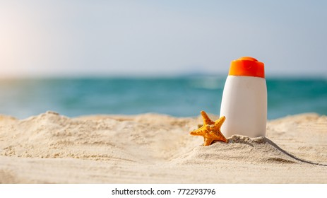 Bottle of sunscreen lotion and starfish on tropical beach, Beach accessories and summer concept, copy space