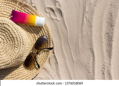 A bottle of sunscreen with sunglasses and panama hat  on a beach, summer skin remedies and protection, vacation at a sea