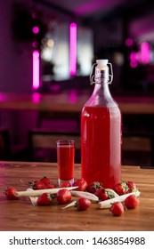 Bottle of sweet strawberry liqueur on a bar counter on wooden table with blurred background