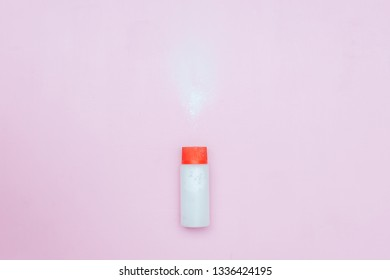 Bottle of Talcum baby powder on pink background. Powder spilled from white container, top view flatlay. red lid