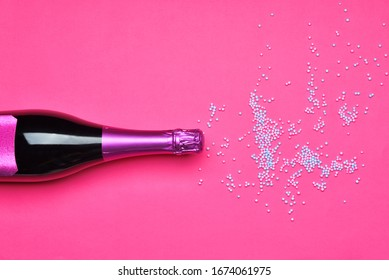Bottle of tasty champagne with sprinkles on color background
