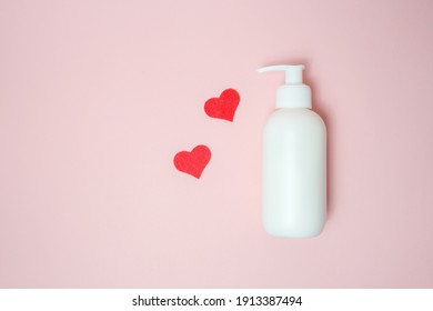A bottle with a thick cream without a lid on a pink background, beside lie small hearts in red.