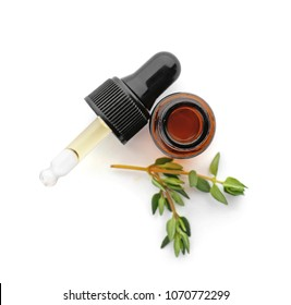 Bottle with thyme essential oil and fresh herb on white background