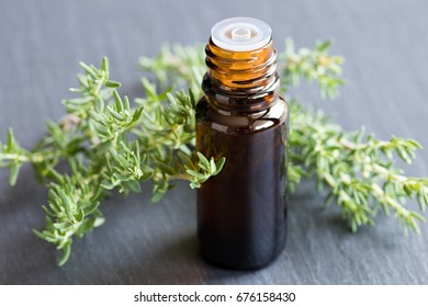 A bottle of thyme essential oil with fresh thyme twigs on a gray background