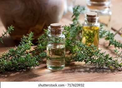 A bottle of thyme essential oil with fresh thyme twigs and other bottles in the background