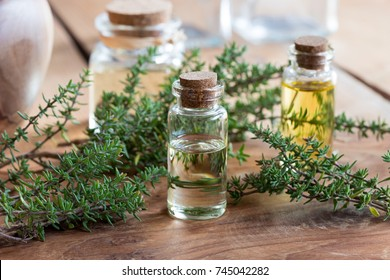 A bottle of thyme essential oil on a wooden table, with fresh thyme twigs and bottles in the background
