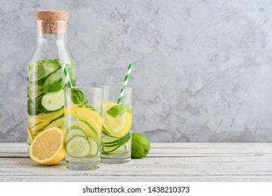 Bottle and two glasses with infused water with cucumber, lemon, lime and basil on gray background