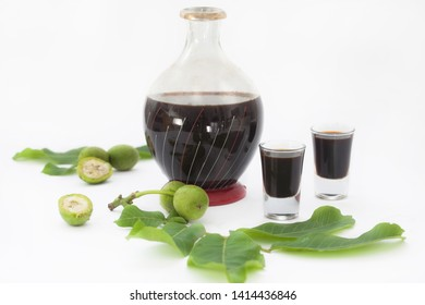 Bottle and two glasses with walnut liquor. Homemade wallnut liquer on white background.