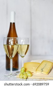 Bottle and two glasses of white wine, white grape and blue cheese on a wooden background