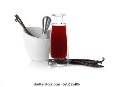 Bottle with vanilla extract, sticks and mortar on white background