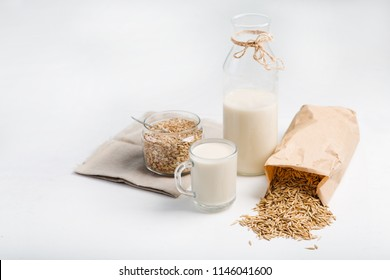 bottle of  vegan oat milk and Oat flakes on a table, space for text.
