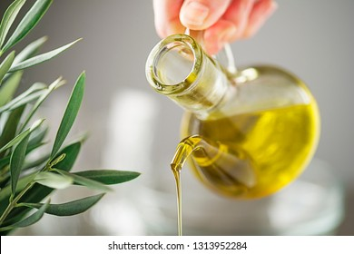 Bottle of virgin olive oil pouring close up