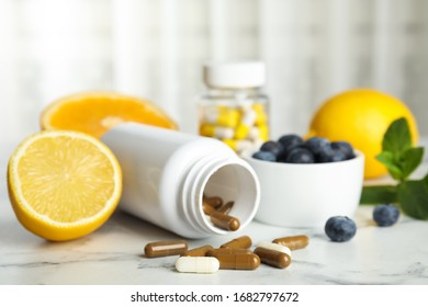Bottle with vitamin pills, blueberries and lemon on white marble table