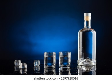 bottle of vodka with glasses and ice on a black background