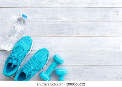 bottle of water, blue sneakers and blue dumbbells  on a white wooden background, sport equipments, fitness items from above.