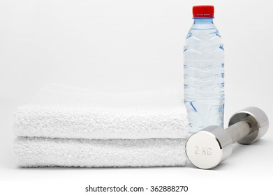 Bottle of water, dumbbell and towel. Isolated on white background
