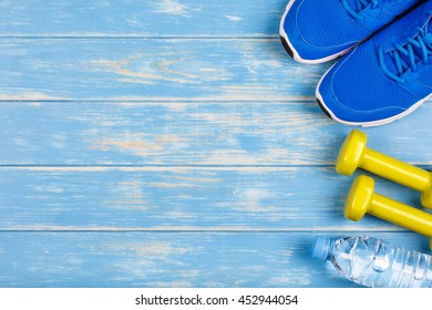 Bottle of water, dumbbells, sport shoes and on blue wood background.
