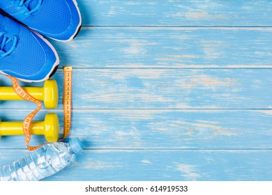 Bottle of water, dumbbells, sport shoes and measure tape on blue wood background.