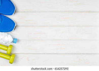 Bottle of water, dumbbells, sport shoes on white wood background. Concept plan.