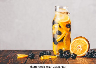 Bottle of Water Infused with Sliced Raw Orange and Fresh Blackberry. Ingredients on Wooden Table.