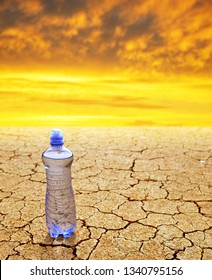 Bottle of water on dry cracked soil at sunset. Concept of global warming.