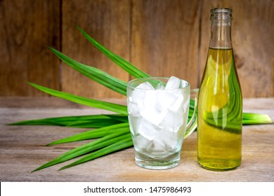 Bottle of water pandan juice and glass of ice with green pandan leaf isolated on rustic wood table background. Natural herbal plant, fragrant screw pine and healthy drinks concept. Vintage style.