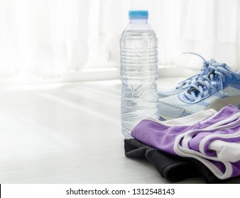 A bottle of water, sport shoes and sportwear with window light.  Sport lifstyle concept