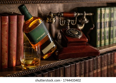 Bottle of whiskey and an antique telephone on a bookshelf, vintage, retro style photo