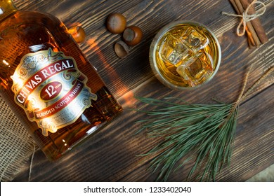 Bottle of whiskey Chivas Regal and glass of whiskey with cubics ice on dark rustic wooden background