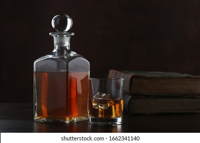 Bottle of whiskey with glass and old books on brown background. Closeup