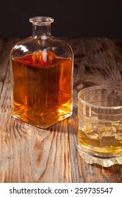Bottle of whiskey and a glass on a wooden table